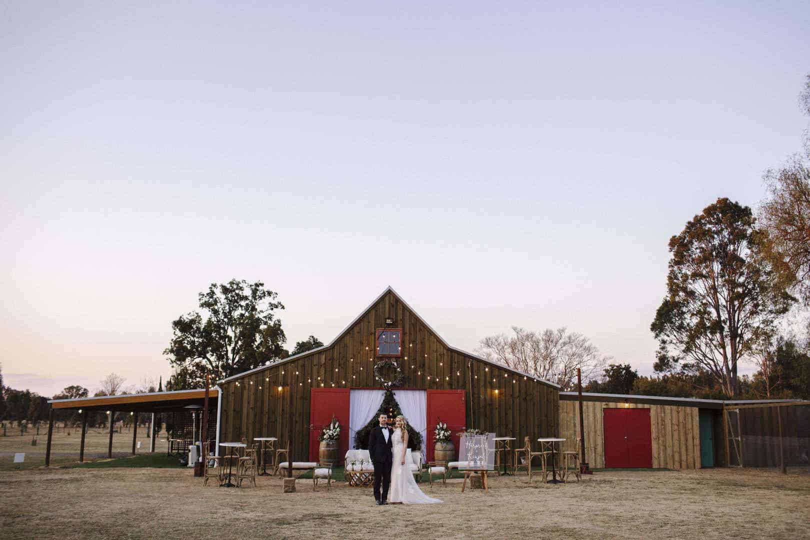 Bride and groom in front of decorated barn