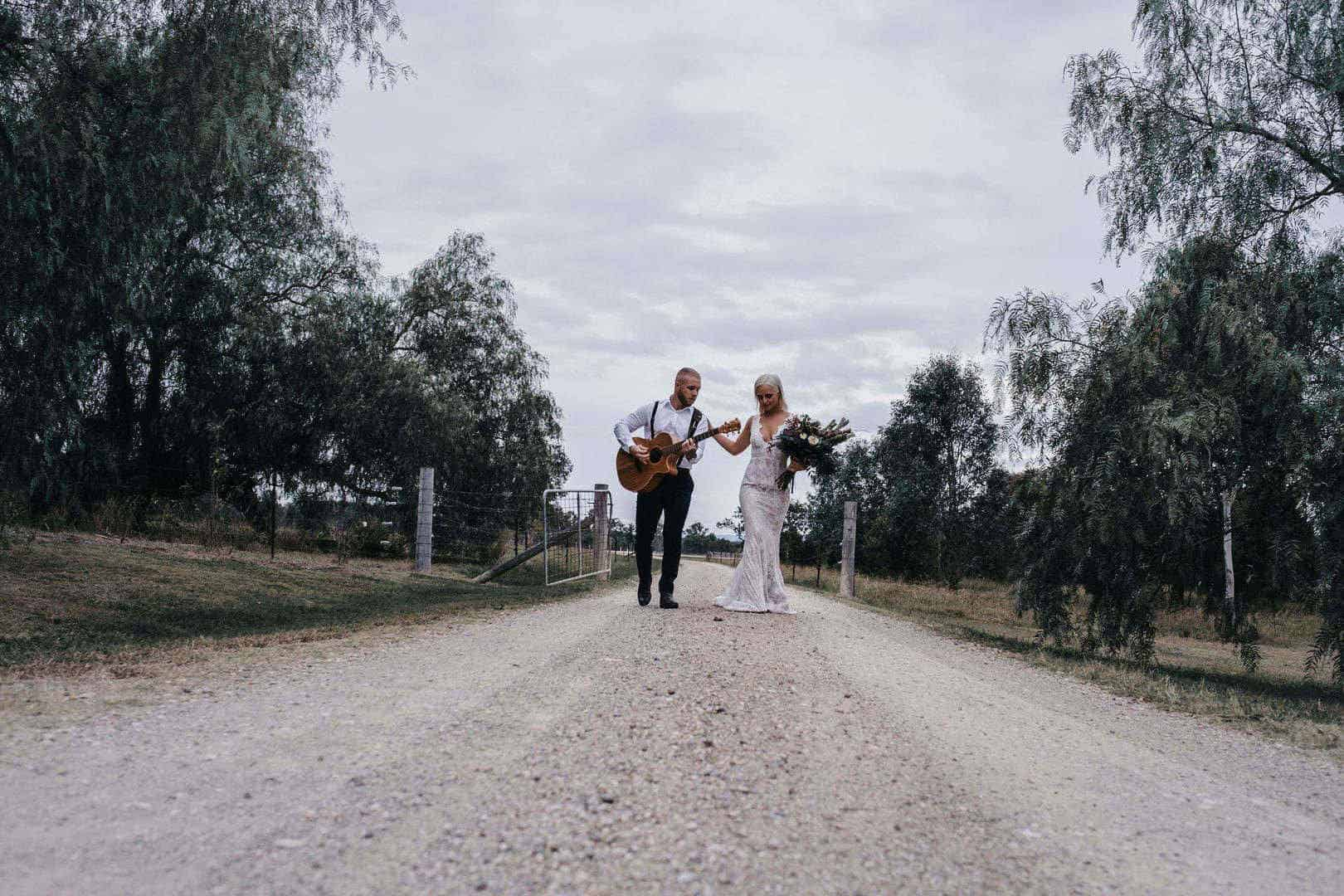Guitarist and bride walking on a path