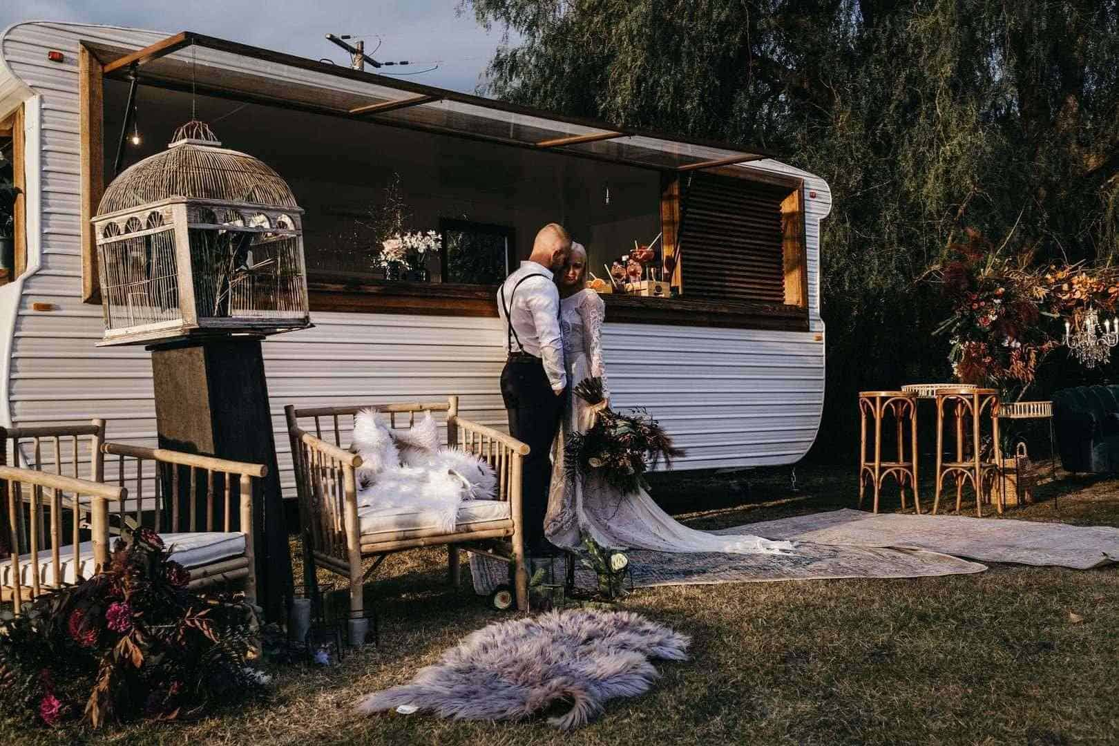 Bride and groom in front of a caravan