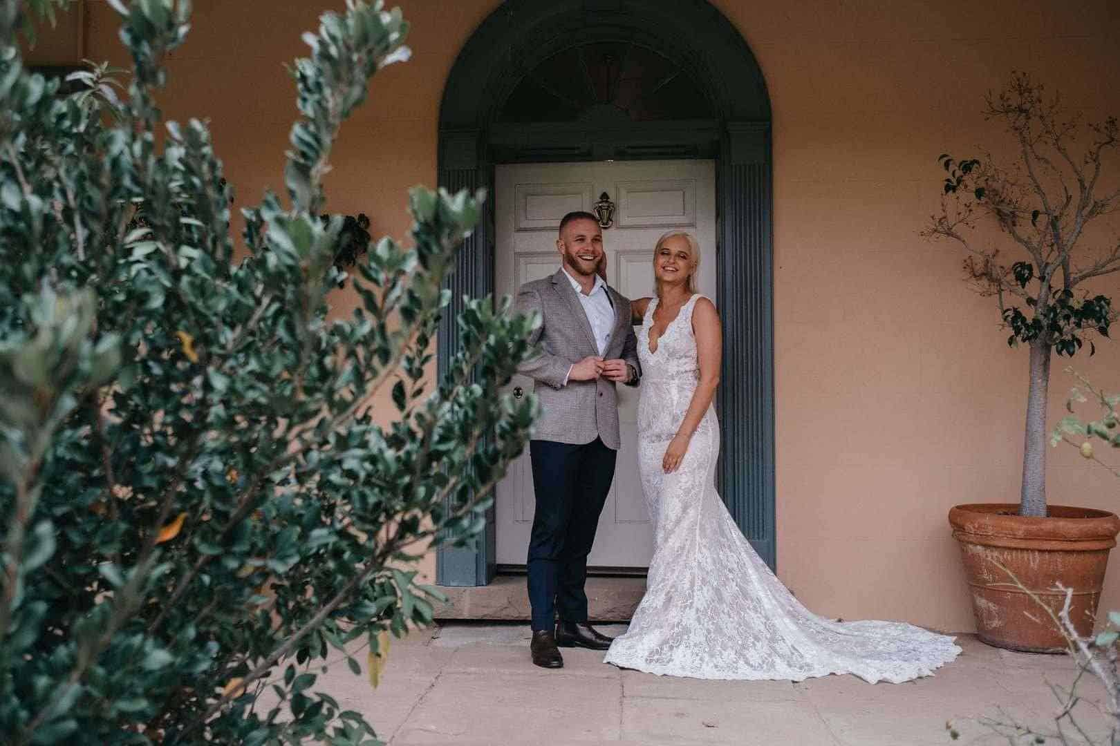Happy bride and groom in front of a door